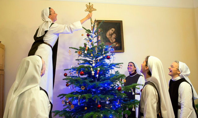 Catholic nuns of the Nyolc Boldogsag Kozosseg (Community of the Eight Bliss) decorate a Christmas tree in a parish of the Church of Perpetual Adoration (Orokimadas-templom) in Budapest, Hungary, 24 December 2016. (Photo by Bea Kallos/EPA)