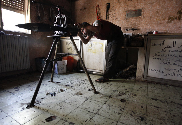 A Free Syrian Army fighter works as he prepares a rocket in a makeshift weapon factory in Aleppo September 9, 2013. (Photo by Loubna Mrie/Reuters)