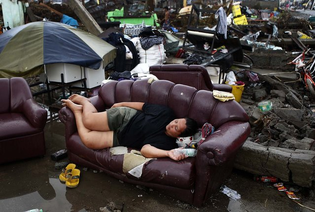 A typhoon victim rests on a sofa at the ruins of her family's home in Palo, Leyte province, on November 12. (Photo by Erik De Castro/Reuters)