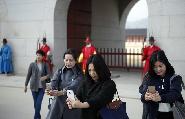 Women take a selfie in front of workers wearing traditional dress while attending the daily re-enactment of the changing of the Royal Guards at the main entrance of Gyeongbok Palace in central Seoul March 16, 2015. (Photo by Kim Hong-Ji/Reuters)