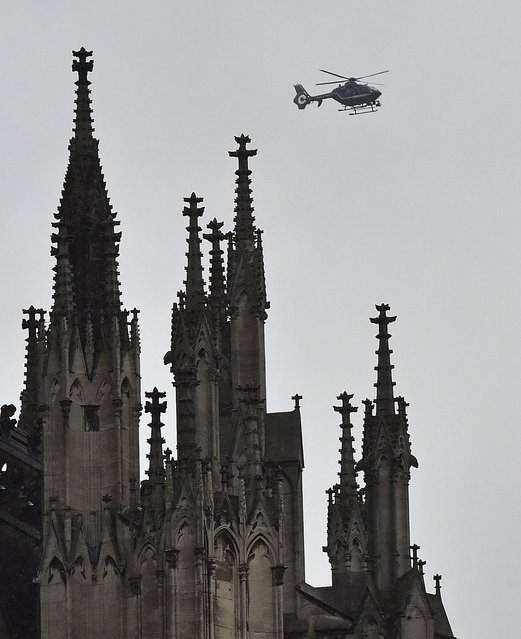 A police helicopter  flies near the Cologne cathedral during the start of the street carnival in Cologne, Germany, on Thursday, February 4, 2016. (Photo by Martin Meissner/AP Photo)