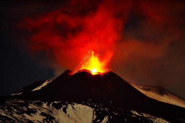 In this photo taken on Saturday, November 16, 2013, Mt. Etna, Europe's most active volcano, spews lava during an eruption as seen from Acireale, near the Sicilian town of Catania, Italy. (Photo by Carmelo Imbesi/AP Photo)