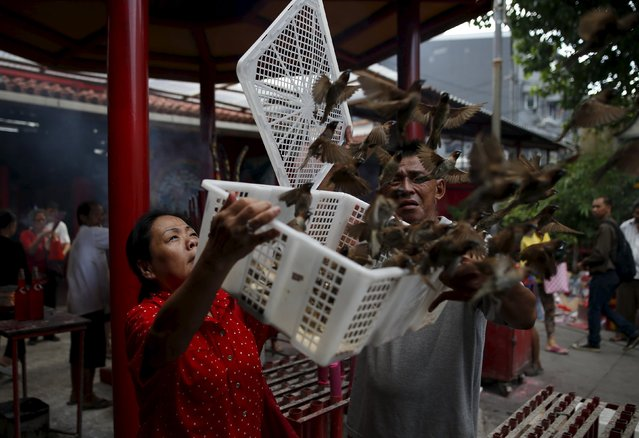 A woman release birds for good fortune at Dharma Bhakti Temple on the first day of the Lunar  New Year in Jakarta, Indonesia February 8, 2016. (Photo by Darren Whiteside/Reuters)