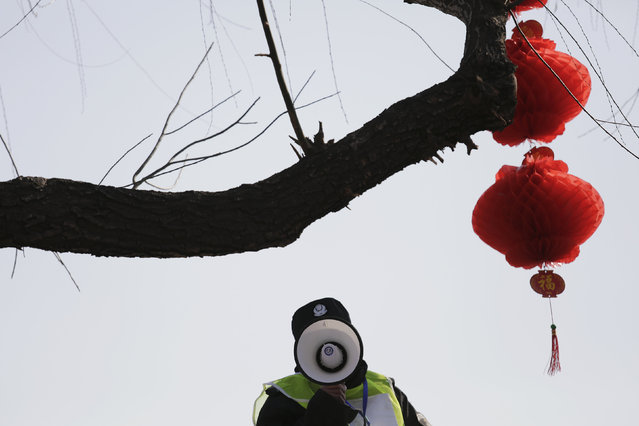 A security agent gives instructions to visitors at the Longtan park as the Chinese Lunar New Year, which welcomes the Year of the Monkey, is celebrated in Beijing, China February 9, 2016. (Photo by Damir Sagolj/Reuters)
