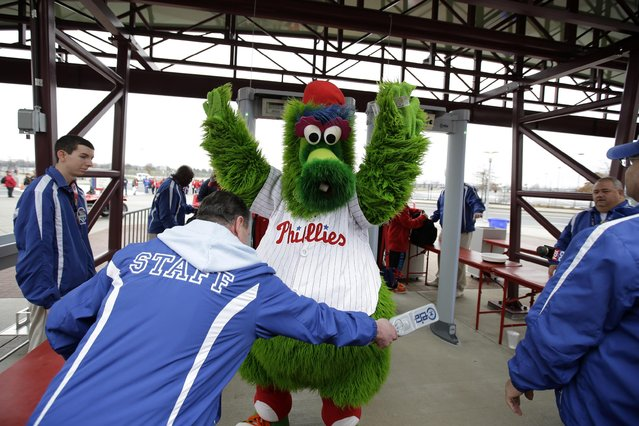 The Philadelphia Phillies' mascot, the Phillie Phanatic, is screened by security personnel for the media before an exhibition baseball game against the Pittsburgh Pirates, Friday, April 3, 2015, in Philadelphia. Citizens Bank Park has installed walk-through metal detectors to comply with Major League Baseball's new rule that all spectators be scanned before entering its stadiums. (Photo by Matt Slocum/AP Photo)
