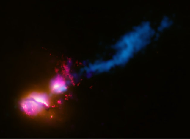 This composite image shows the jet from a black hole at the center of a galaxy striking the edge of another galaxy, the first time such an interaction has been found. In the image, data from several wavelengths have been combined. X-rays from Chandra (colored purple), optical and ultraviolet (UV) data from Hubble (red and orange), and radio emission from the Very Large Array (VLA) and MERLIN (blue) show how the jet from the main galaxy on the lower left is striking its companion galaxy to the upper right. (Photo by Reuters/NASA/CXC/CfA/D.Evans)