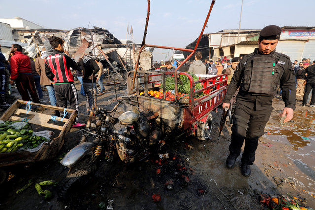 An Iraqi policeman inspects the site of a car bomb attack at a vegetable market in eastern Baghdad, Iraq January 8, 2017. (Photo by Wissm al-Okili/Reuters)