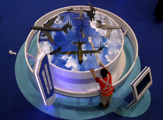A worker cleans model aircrafts on display at the Singapore Technology (ST) Engineering booth during a preview tour of the Singapore Airshow at Changi exhibition center in Singapore February 14, 2016. (Photo by Edgar Su/Reuters)