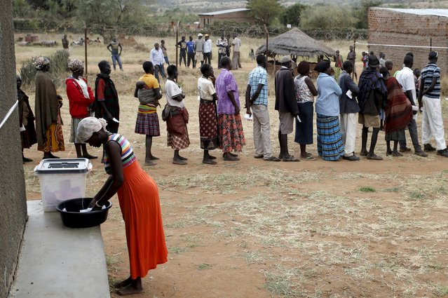 A Karamojong tribeswoman casts her ballot at a polling station during the presidential elections in a village near Kaabong in Karamoja region, Uganda, February 18, 2016. (Photo by Goran Tomasevic/Reuters)