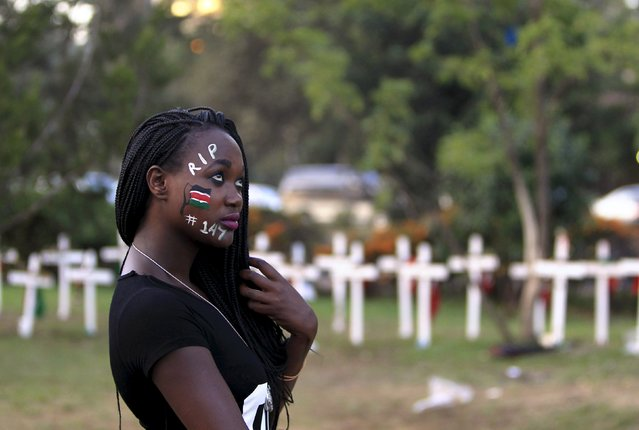 """A student wearing facepaint walks past wooden crosses in memory of the Garissa university students who were killed by gunmen, at a memorial concert at the """"Freedom Corner"""" in Kenya's capital Nairobi April 14, 2015. Kenya gave the United Nations three months to remove Dadaab camp, housing 350,000 registered Somali refugees, as part of its response to the killing of 148 people in nearby Garissa by a Somali Islamist group. (Photo by Noor Khamis/Reuters)"""