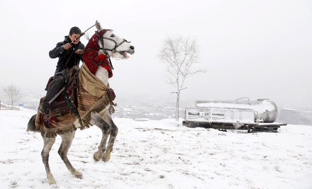 An Afghan boy rides on a horse in a snow covered neighborhood in Kabul, Afghanistan, 15 January 2017. Afghanistan is experiencing harsh winters with temperatures falling well below freezing in many parts of the country. (Photo by Jawad Jalali/EPA)