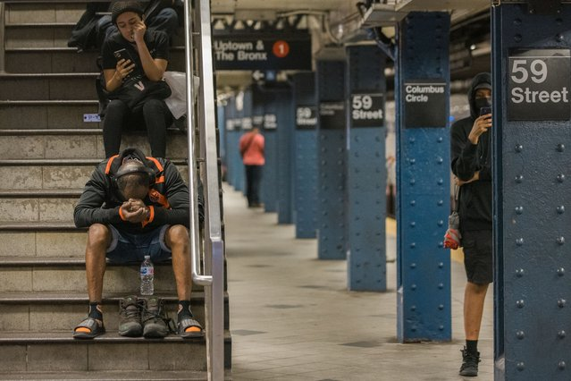 People wait for the subway after flash flood in Manhattan, New York on September 2, 2021. (Photo by Jeenah Moon for The Washington Post)
