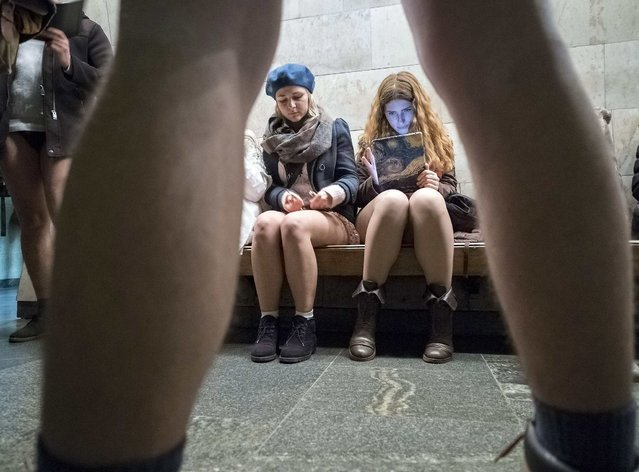 """Passengers without pants wait on a underground platform during the """"No Pants Subway Ride"""" in Kiev January 12, 2014. The event is an annual flash mob and occurs in different cities around the world in January, according to its organizers. (Photo by Gleb Garanich/Reuters)"""