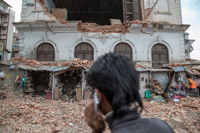 A young man speaks on the phone in front of a collapsed building in the city center following an earthquake on April 25, 2015 in Kathmandu, Nepal. (Photo by Omar Havana/Getty Images)