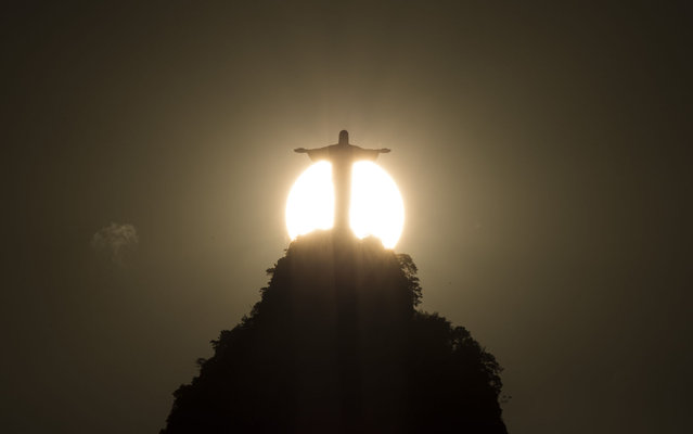 Christ the Redeemer statue is silhouetted against a setting sun in Rio de Janeiro, Brazil, Wednesday, January 22, 2014. Rio de Janeiro's famed Christ statue is being repaired after two fingers and its head were chipped during recent lightning storms. Workers began examining the 125-foot statue on Tuesday. After inspecting the damage up close, officials say it'll take about four months to repair. (Photo by Felipe Dana/AP Photo)