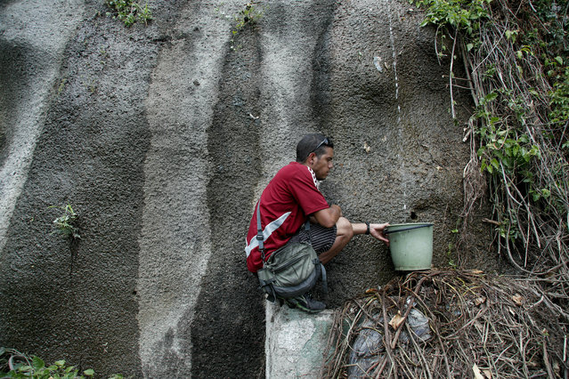 A man collects water in Avila National Park during rolling blackouts, which affects the water pumps in people's homes and apartment buildings, in Caracas, Venezuela, Sunday, March 10, 2019.  Venezuelans reached new levels of desperation Sunday as the country's worst blackouts took their toll, gathering in larger numbers than usual at springs in the mountains of Caracas to collect water and scrounging for scarce cash to pay for food in the few shops that were open. (Photo by Eduardo Verdugo/AP Photo)