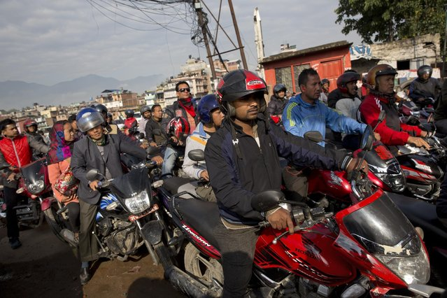 Nepalese queue at a gas station in Kathmandu, Nepal, Monday, April 27, 2015. The city is still experiencing a series of aftershocks following a massive earthquake on Saturday. After two days without power, anxious residents have been standing in long queues outside gas stations to store up on some fuel. (Photo by Bernat Armangue/AP Photo)