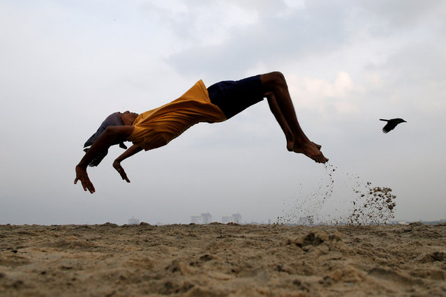 A boy practices somersaulting as he exercises at a beach in Kochi, India, March 11, 2019. (Photo by Sivaram V/Reuters)