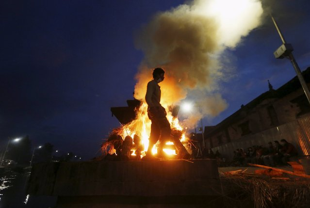 A man walks next to the burning pyre of a family member, who died in Saturday's earthquake, during the cremation along a river in Kathmandu, Nepal April 28, 2015. (Photo by Adnan Abidi/Reuters)