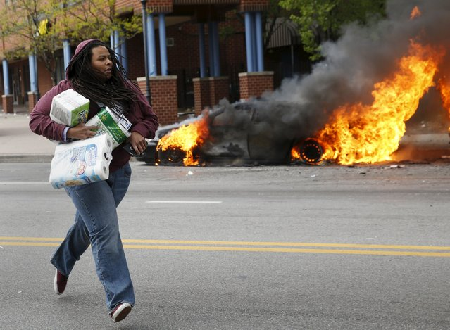 A woman with goods looted from a store runs past burning vehicles during clashes in Baltimore, Maryland April 27, 2015. Seven Baltimore police officers were injured on Monday as rioters threw bricks and stones and burned patrol cars in violent protests after the funeral of Freddie Gray, a black man who died in police custody. (Photo by Shannon Stapleton/Reuters)