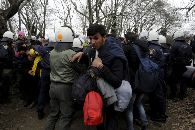 Migrants pass through a Greek riot police cordon as they look for a way to cross the Greek-Macedonian border, near the village of Idomeni, Greece, March 14, 2016. (Photo by Alexandros Avramidis/Reuters)