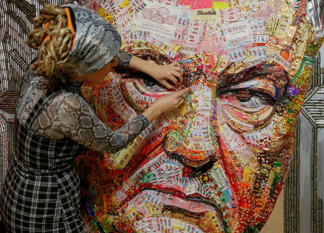 Ukrainian artist Dariya Marchenko works on a portrait of Ukraine's President Petro Poroshenko named 'The Face of Corruption' which is made of wrappers from more than 20 kilograms of Roshen candies and empty shell cartridges brought from the frontline of a military conflict in the east of the country, in Kiev, Ukraine March 27, 2019. (Photo by Valentyn Ogirenko/Reuters)