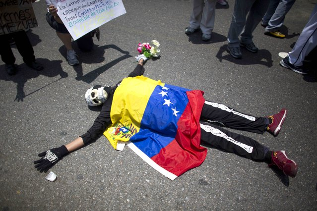 An opposition demonstrator dressed in a skeleton costume with a Venezuelan national flag draped over his body, lies on the pavement, during a May Day march in Caracas, Venezuela, Friday, May 1, 2015. (Photo by Ariana Cubillos/AP Photo)