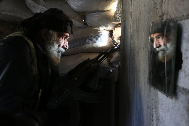 Syrian Mahmoud Al- Khatib, a fighter from the Jaish al- Islam (Islam Army), the foremost rebel group in Damascus province who fiercely oppose both the Syrian regime and the Islamic State group, holds a position inside a building on the frontline in the town of Bilaliyah, east of the capital Damascus, on February 4, 2017. Fifty- year- old Al- Khatib says he' s been fighting against the regime since the beginning of the conflict in Syria. He was wounded four times and spends his free time taking care of stray dogs. (Photo by Amer Almohibany/AFP Photo)