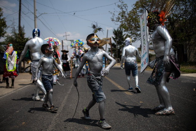 "Young residents of San Nicolas de los Ranchos community, in Puebla state, Mexico with their bodies painted with oil and using masks parade and dance as ""Xinacates"" in the town's traditional carnival, on March 31, 2019. A ritual that originally was performed for good harvests, this year is also to honour the nearby Popocatepetl volcano, which increasing activity with ashes, gases and incandescent material in recent days has put the Mexican authorities on alert. (Photo by Pedro Pardo/AFP Photo)"