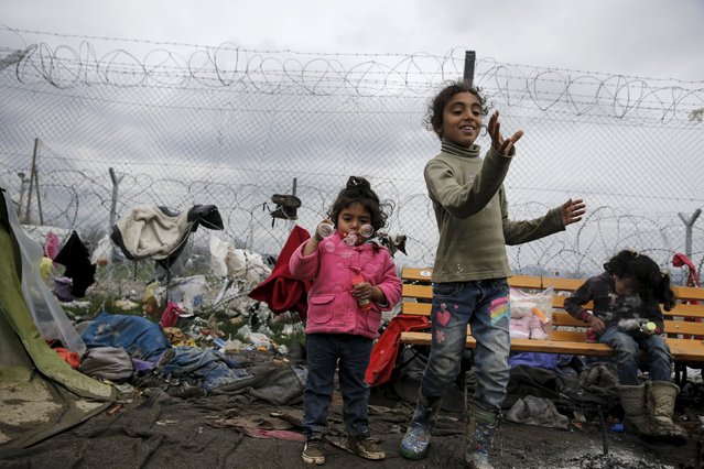 Syrian refugee girls blow soap bubbles next to the border fence at the Greek-Macedonian border, at a makeshift camp for refugees and migrants near the village of Idomeni, Greece March 16, 2016. (Photo by Alkis Konstantinidis/Reuters)
