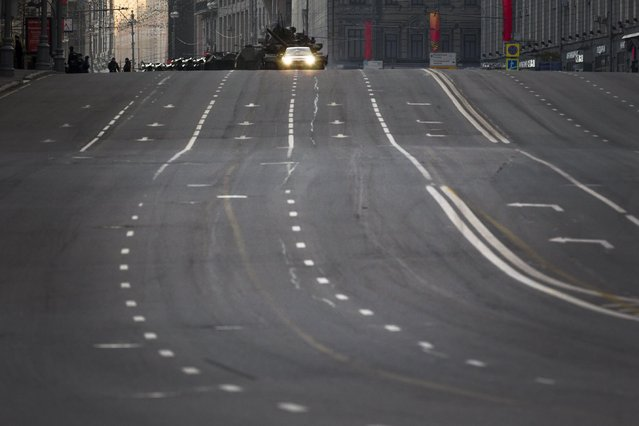 A traffic police car leads Russian military vehicles making their way throughout the empty main street to Red Square during a rehearsal for the Victory Day military parade which will take place at Moscow's Red Square on May 9 to celebrate 70 years after the victory in WWII, in Moscow, Russia, Monday, May 4, 2015. (Photo by Alexander Zemlianichenko/AP Photo)
