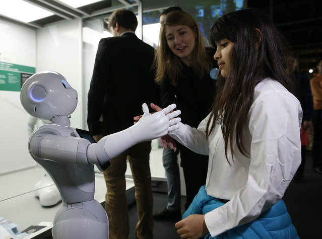 Charllotte Abbot shakes hands with Pepper an interactive French-Japanese robot, during a press preview for the Robots exhibition held at the Science Museum in London, Tuesday, February 7, 2017. (Photo by Alastair Grant/AP Photo)
