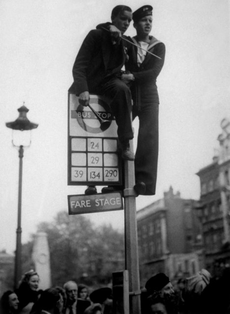 8th May 1945: A sailor and a civilian clamber on top of a bus stop in Whitehall, London, during the VE Day celebrations. (Photo by Keystone/Getty Images)