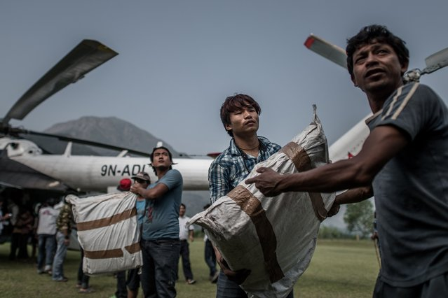 Workers load relief supplies in a helicopter for the World Food Programme (WFP) in Deurali village of Nepal's Gorkha district on May 6, 2015. (Photo by Philippe Lopez/AFP Photo)