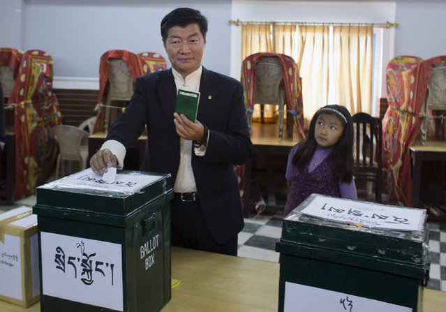 Lobsang Sangay, the incumbent prime minister of the Tibetan government-in-exile casts his vote as his daughter looks on in Dharamsala, India, Sunday, March 20, 2016. Tens of thousands of Tibetan exiles are voting around the world Sunday to elect a new prime minister and parliament for a second time since the Dalai Lama stepped down as head of the government in 2011 to focus on his role as a spiritual leader. (AP Photo /Ashwini Bhatia)