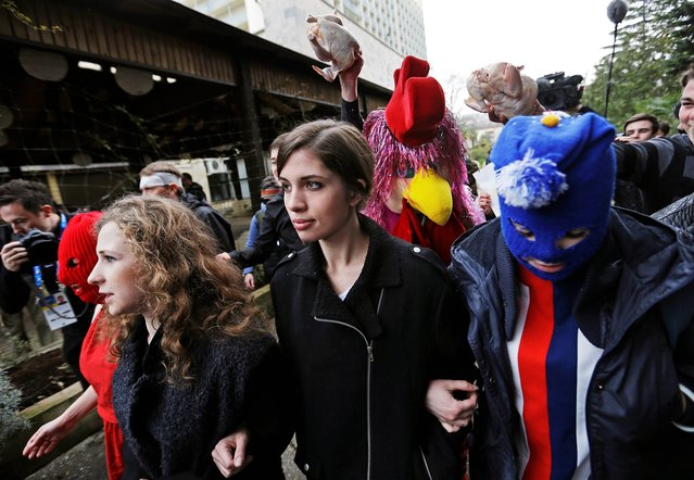 p*ssy Riot members Nadezhda Tolokonnikova, center, and Maria Alekhina, left, arrive for a press conference while followed by a person in a chicken costume protesting the punk group – who have feuded with Vladmir Putin's government for years – Thursday, Feb. 20, 2014, in Sochi, Russia. (Photo by David Goldman/AP Photo)