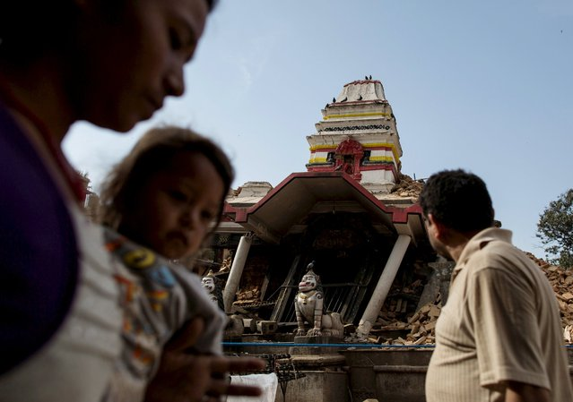 People walk past a collapsed temple following last week's earthquake at Khokana in Lalitpur, Nepal, May 2, 2015. (Photo by Danish Siddiqui/Reuters)