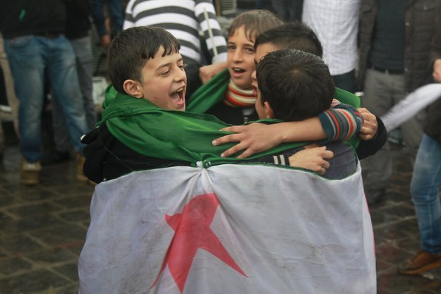 Children covering themselves with an opposition flag dance as they take part in a protest marking the fifth anniversary of the Syrian crisis in the old city of Aleppo, Syria March 15, 2016. (Photo by Abdalrhman Ismail/Reuters)