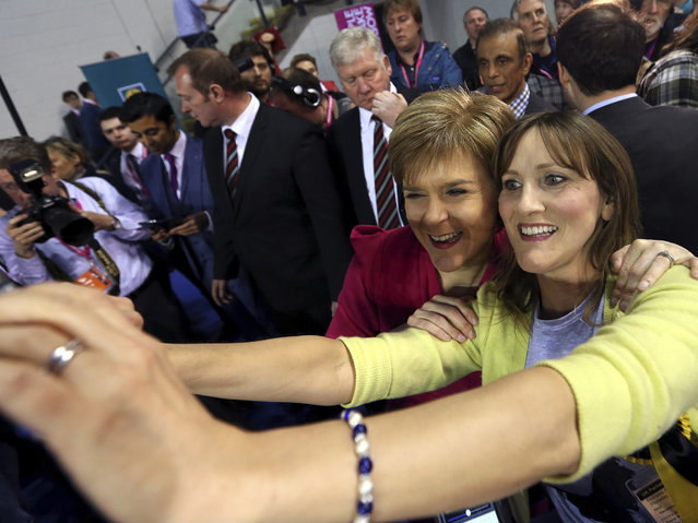 First Minister of Scotland and Scottish National Party leader Nicola Sturgeon, second right, poses for photographs at the count of Glasgow constituencies for the general election in Glasgow, Scotland, Friday, May 8, 2015. (Photo by Scott Heppell/AP Photo)