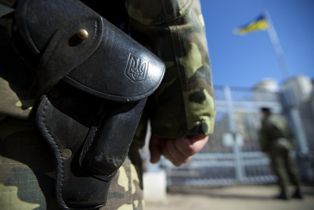 Ukrainian state emblem is seen on a gun's holster as soldiers guard naval base in the village of Novoozernoye, some 91 km west of Crimean capital Simferopol, Ukraine, on Monday, March 3, 2014. Ukraine says Russian forces controlling the strategic region of Crimea are demanding that the crew of two Ukrainian warships in Sevastopol's harbor must surrender. (Photo by Ivan Sekretarev/AP Photo)
