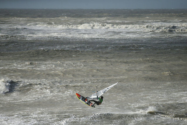 A windsurfer braves the sea off East Sussex in Newhaven, UK on March 28, 2016. (Photo by Steve Parsons/PA Wire)