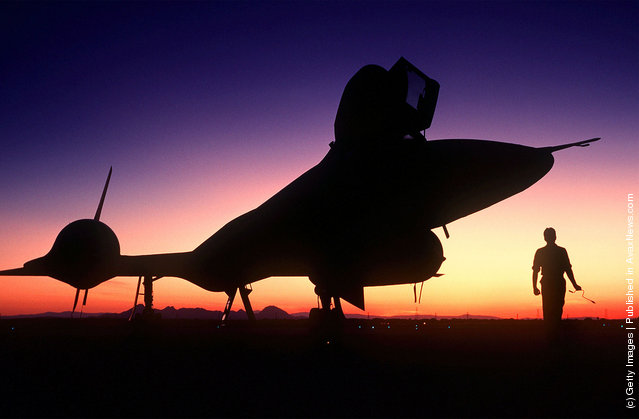 A right front view of an SR-71B Blackbird strategic reconnaissance training aircraft, silhouetted on the runway at sundown