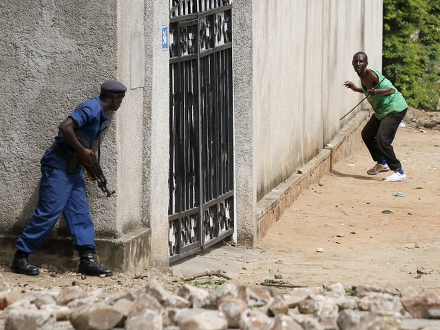 Policemen clash with protesters near a parliament building during a protest against Burundian President Pierre Nkurunziza's decision to run for a third term in Bujumbura, Burundi May 13, 2015. A Burundian general said on Wednesday he had deposed Nkurunziza for seeking an unconstitutional third term in office, and was working with civil society groups to form a transitional government. (Photo by Goran Tomasevic/Reuters)