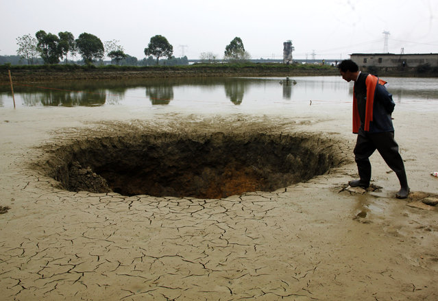 A man looks into a sinkhole which appeared in his fish pond in Guiping, Guangxi Zhuang Autonomous Region, March 29, 2016. (Photo by Reuters/Stringer)
