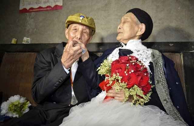 Yan Zhengming (L), 94, kisses the hand of his wife Zhou Suqing, 90, during their wedding ceremony at their home, on the 70th anniversary of their marriage, in Quxian county of Dazhou, Sichuan province, China, May 15, 2015. (Photo by Reuters/Stringer)
