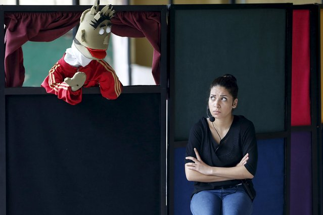 An actress performs in a puppet theater show at an UNRWA school in Burj al-Barajneh in Beirut May 14, 2015. The Arab Puppet Theatre Foundation (APTF) is touring the 68 schools of the UN refugee agency's UNRWA and performs for all 39,000 Palestinian students in Lebanon, in a project with UNICEF and UNRWA. (Photo by Mohamed Azakir/Reuters)