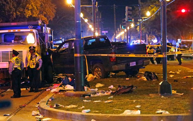 Police stand next to a pickup truck that slammed into a crowd and other vehicles, causing multiple injuries, coming to a stop against a dump truck, during the Krewe of Endymion parade in New Orleans, Saturday, February 25, 2017. (Photo by Gerald Herbert/AP Photo)