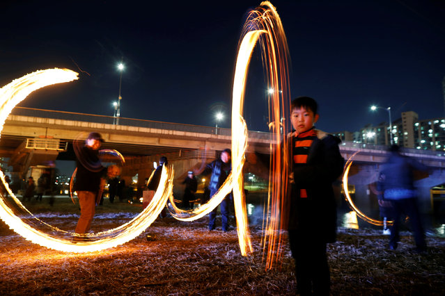 """Participants whirl cans filled with burning wood chips during a celebration ahead of """"Jeongwol Daeboreum"""" (Great Full Moon), which is a traditional Korean holiday that celebrates the first full moon of the lunar calendar, at a park in Seoul, South Korea, February 17, 2019. (Photo by Kim Hong-Ji/Reuters)"""