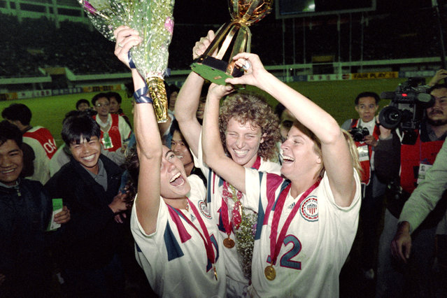 Michelle Akers-Stahl (C) who scored two goals for the US to win the first FIFA World Championship for Women's Football on November 30, 1991, holds the trophy together with teammates Julie Foudy (L) and Carin Jennings (R). The US won the championship by beating Norway 2-1. The FIFA Women's World Cup is recognized as the most important International competition in women's football and is played amongst women's national football teams of the member states of FIFA. Contested every four years, the first Women's World Cup tournament, named the Women's World Championship, was held in 1991, sixty-one years after the men's first FIFA World Cup tournament in 1930. (Photo by Tommy Cheng/AFP Photo)