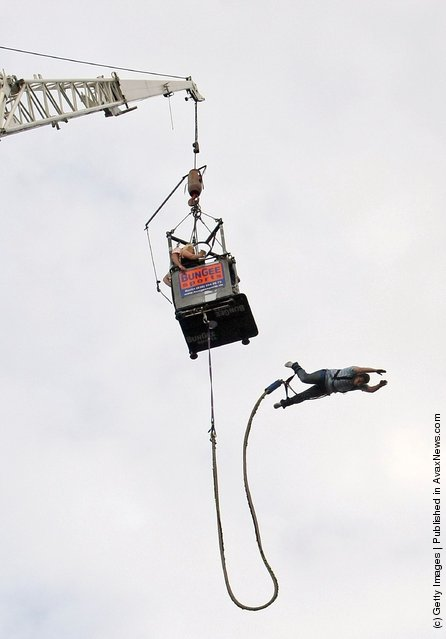 A visiitor bungee jumps during an outdoor festival to celebrate German Unity Day
